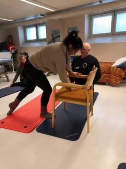 Koulutustilanne, jossa nainen nojaa tuoliin ja kinestetiikkakouluttaja Seppo Hauta tarkkailee. Taustalla myös opiskelija tarkkailemassa.