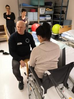 Kinestetiikkakouluttaja Seppo Hauta istuu edessä pyörätuolia istuvaa naista, joka on selin. Taustalla seisoo kaksi naista tarkkailemassa.