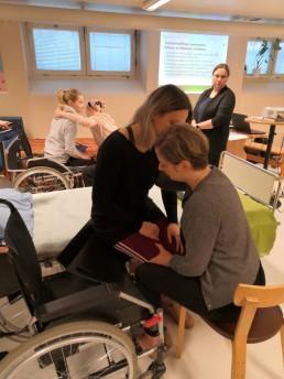 Koulutustilanne, jossa kaksi opiskelijaparia harjoittelee pyörätuolista siirtymistä laitossängylle. Toinen siirtyy ja toinen avustaa.