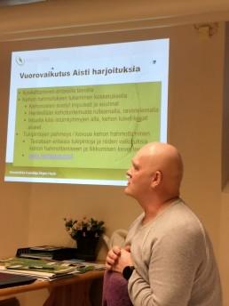 Kinestetiikkakouluttaja Seppo Hauta istuu ja katsoo vasempaan. Taustalla on seinälle heijastettu luentokalvo vuorovaikutus- ja aistiharjoituksista.
