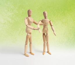 Kaksi puista mallinukkea. Oikeanpuoleinen nukke katsoo eteensä ja vasemman puoleinen on kääntyneenä oikeaa kohti ojentaen käsiään.