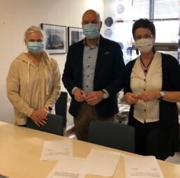 Kolme henkilöä seisoo pöydän takana, kaikilla on maskit kasvoilla, pöydällä on papereita allekirjoitettavaksi.