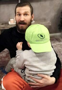 Mies istuu lippalakkipäinen lapsi sylissä, miehen kasvot kameraan, lapsen selkä kameraan