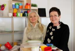 Kirsi Myller-Pirinen ja Virpi Hantikainen seisovat pöydän vieressä. Pöydällä on värikkäitä E. Ahlströmin astioita.