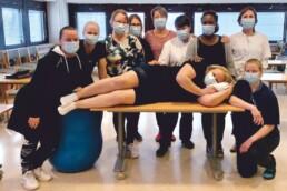 Ryhmäkuva kinestetiikan peruskurssilaisista, kaikilla maskit kasvoilla, keskellä nainen makaa pöydällä ja muut seisovat ympärillä