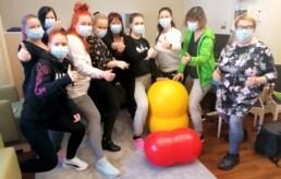 Ryhmäkuvassa kymmenen henkilöä seisoo kaaressa ja kaikki näyttävät peukkua. Kuvan keskellä edessä on kaksi papupalloa, keltainen ja punainen. Kaikilla henkilöillä on maskit kasvoilla.